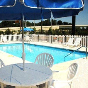 Econo Lodge Pensacola Pool with view of table with umbrella and chairs