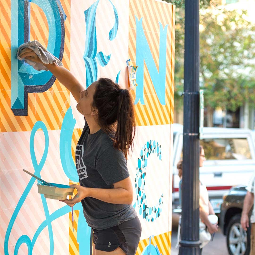 A woman painting on a wall spelling Pensacola